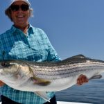 Older Woman Holding Medium Striped Bass