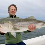 Middle Aged Man Holding Striped Bass Catch