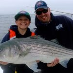 Father and Son with Striped Bass