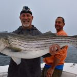 Two Fishermen with a Striped Bass