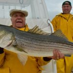 Two Fishermen in Cape Cod with Striped Bass
