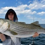 Young Boy Holding Striped Bass