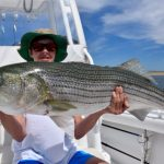 Lady Holding Striped Bass Catch