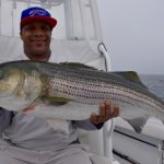 Man Holding Medium Striped Bass Catch