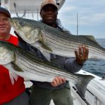 Two Fishermen with Striped Bass Catches