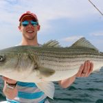 Young Man with Large Striped Bass Catch