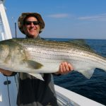 Man Smiles with His Large Striped Bass