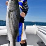 Small Boy Holding Large Striped Bass