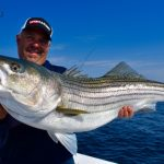 Older Man Holding Striped Bass