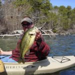 Man Fishing in a Kayak with Large Fish